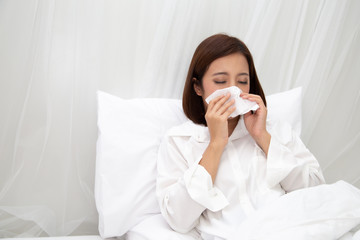 Young Asian woman sneezing in a tissue on the white bed at bedroom, Flu and allergy concept