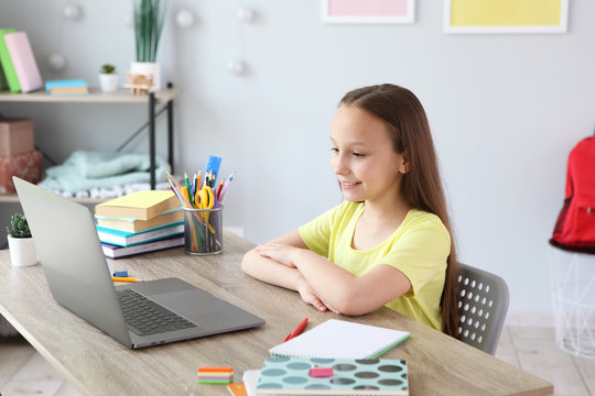 A child learns online at home through a modern laptop on the Internet.