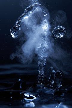 Boiling water splash with steam on dark blue background closeup