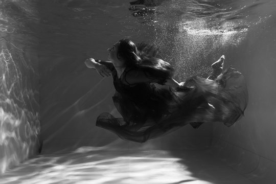 Black and white photo. Beautiful girl underwater in a red dress swims in the pool. Tenderness and elegance. Bubbles and a lot of water