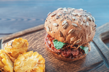 Delicious and juicy Burger as a symbol of American fast food and super-calorie diet. Served on a...