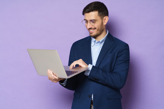 Young businmessman wearing trendy smart casual suit, standing with open laptop in hands, smiling at content on screen, isolated on purple background