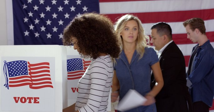 Four people of different demographics, young Hispanic woman in front, filling in ballots and casting votes in booths at polling station, US flag on wall at back