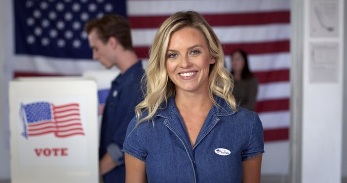 """MCU Young blonde Caucasian woman in denim dress and with an """"I Voted"""" sticker, smiles standing proud in front of polling booths with US flag."""