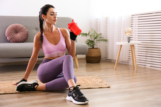 Stay at home training concept. Young attractive woman of athletic build drinking post workout protein shake. Beautiful female in feminine sportswear holding red shaker. Close up, copy space background