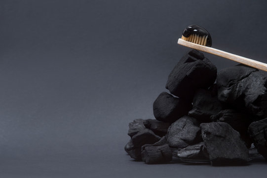 Natural toothpaste activated charcoal and bamboo toothbrush on black  background. Zero waste concept.