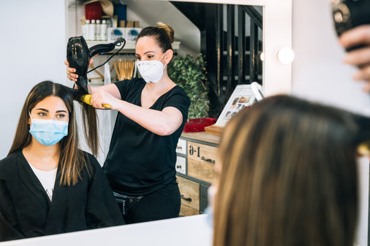 Hairdresser drying a beautiful girl's hair reflected in the mirror