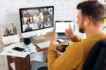 Video conference. Business partners communicate via video using laptop. The guy talks with his business partners appearance about plans and strategy. Distant work