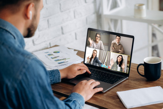 Work online by a video conference with colleagues. A man in a stylish wear sits at his workplace at home and solves working issues on video communication with business partners