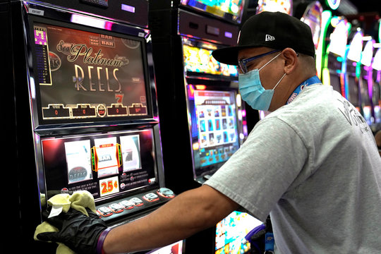 A member of the cleaning staff sanitizes a slot machine at the recently reopened Lucky Star Casino in El Reno