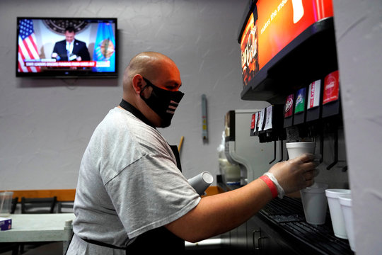 An employee wearing a mask fills drinks for customers at the recently reopened Lucky Star Casino in El Reno