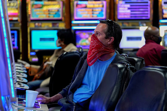 A man wearing a bandana plays a slot machine at the recently reopened Lucky Star Casino in El Reno