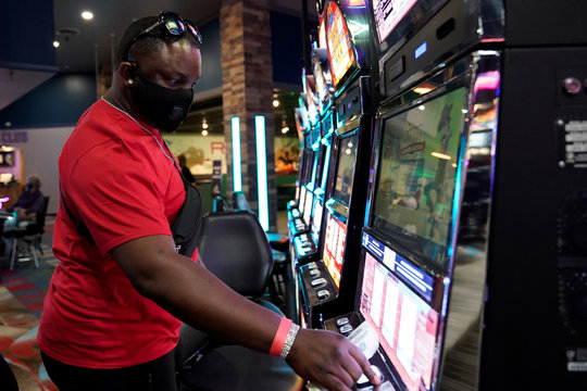A man wearing a mask plays a slot machine at the recently reopened Lucky Star Casino in El Reno
