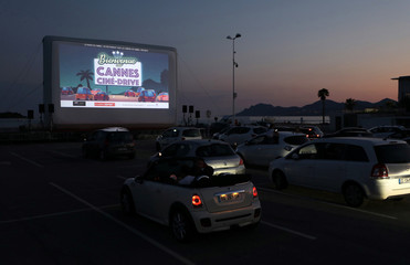 People sit in their cars to watch E.T. at drive-in cinema in Cannes