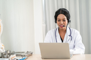 african woman doctor in headset taking calling on her headset microphone online for a ache patient
