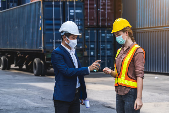 The supervisor wearing a protective surgical mask, standing for a physical examination and pressing the alcohol gel to colleague before into workplace at the warehouse container