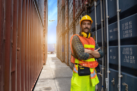 Engineer beard man standing with ware a yellow helmet to control loading and check a quality of containers from Cargo freight ship for import and export at shipyard or harbor