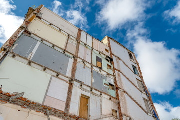 The high wall of the destroyed building against the blue sky
