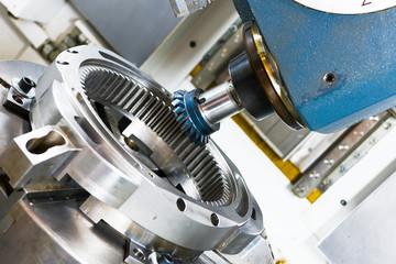 A modern CNC milling machine makes a large gear wheel.