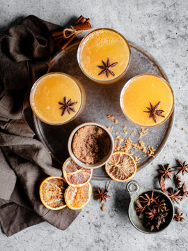 Overhead shot of three glasses of an orange spiced drink on a silver tray, garnished with star anise and surrounded by blood oranges, cinnamon sticks, a grey napkin, and a small bowl of brown sugar