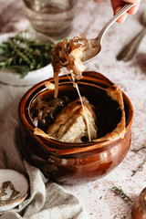 Cheesy vegetarian French onion soup into a bowl