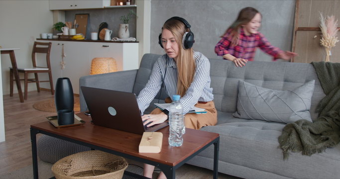 Young happy Caucasian mother is distracted trying to work from home on laptop with two noisy children needing attention.