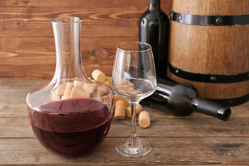 Decanter with bottles of wine and glass on wooden background