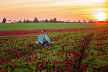Beautiful children, brothers in gorgeous crimson clover field on sunset,