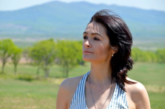 Portrait of 45 year old caucasian brunette woman looking away, with bare shoulders on a green field against the background of the mountains. Copy space