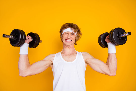 Close-up portrait of his he nice attractive sportive guy sportsman doing work out lifting heavy barbell self developing isolated over bright vivid shine vibrant yellow color background