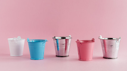 Mini colored tin pails or buckets on pink background with copy space for household items concept