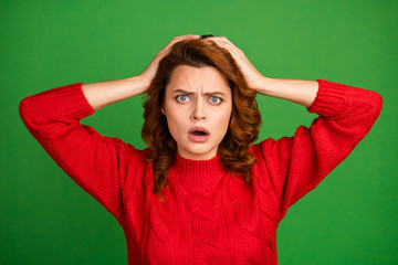Portrait of astonished frustrated woman hear horrible work mistake novelty impressed scream omg touch hands redhead wear knitted pullover isolated over vivid color background