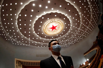 Security member keeps watch at the opening session of CPPCC in Beijing