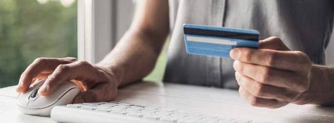 Man hand holding credit card and using laptop at home, Businessman or entrepreneur working, Online...