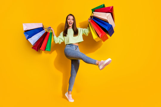 Full size photo of positive cheerful girl enjoy shopping buy many off-sales hold bags wear green good look clothes sneakers isolated bright shine yellow color background