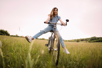 Cheerful young woman riding bicycle in nature