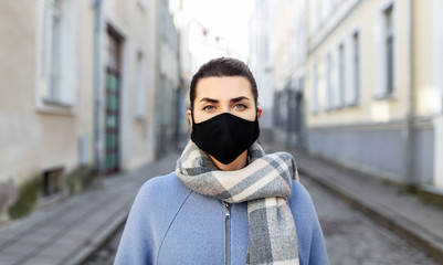 health, safety and pandemic concept - young woman wearing black face protective reusable barrier...
