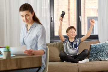 leisure, technology and children concept - happy smiling boy with gamepad playing video game and celebrating success at home