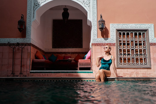 Retreat and vacation. Beautiful young woman relaxing in spa private swimming pool in beautiful moroccan backyard.