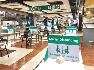 Stores photo Nature BANGKOK, THAILAND- June 21, 2020: Social distancing for COVID-19 disease pandemic prevention in Tesco Lotus food court dining table public area for new normal keeping people distance