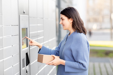 mail delivery and post service concept - happy smiling woman with box at outdoor automated parcel machine choosing operation on touch screen