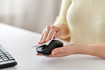 hygiene and disinfection concept - close up of woman hands cleaning computer mouse with paper tissue