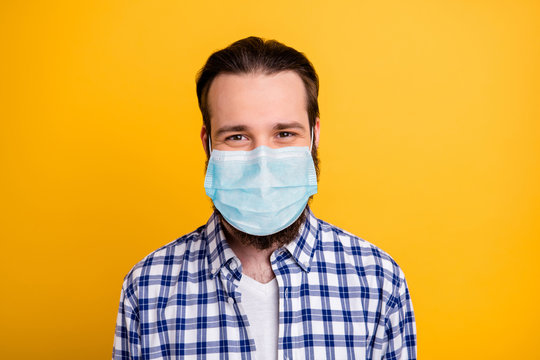Close-up portrait of his he nice cheerful bearded guy wearing breathing mask checked shirt IT expert stay home quarantine isolated bright vivid shine vibrant yellow color background