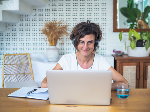 happy smiling remote woman talking and flirting with headset, laptop, notebook, pen and glass in casual outfit sitting on a work desk in her living room in her home office having video chat