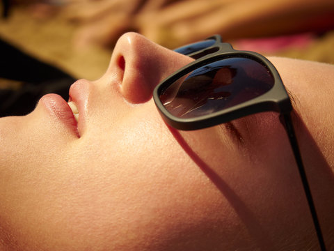 Face portrait of a girl in sunglasses on the beach