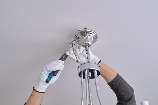Installation ceiling lamp, hands of electrician fixing chandelier