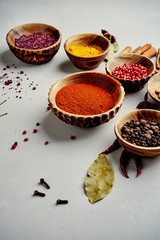 Colorful spices in wood bowls on grey background with copy space. Nature Seasoning Pepper, turmeric, paprika, rosemary, chilly, cardamom, cinnamon, anise, cloves. ingredients.