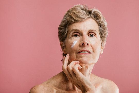 Senior woman using facial cream