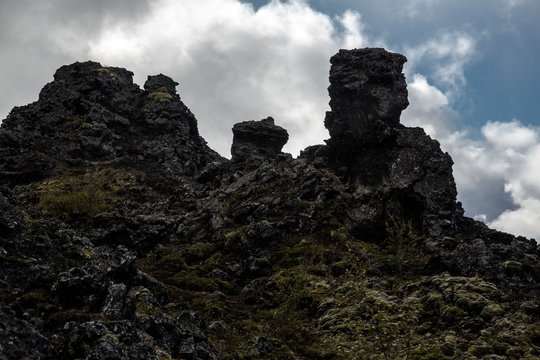 view of Dimmuborgir, a volcanic formation located in the region of Lake Mývatn. The cooled lava formations are black, with some vegetation, while the sky is cloudy