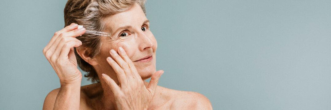 Senior woman applying moisturizer on her eye wrinkles